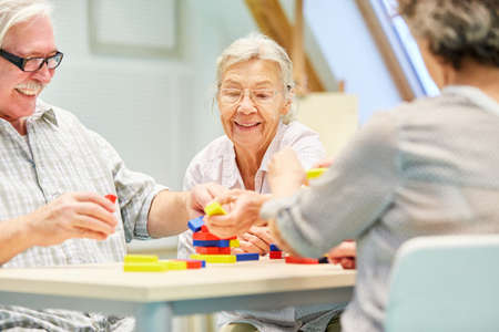 Group of seniors with dementia is having fun playing with building blocks as employment
