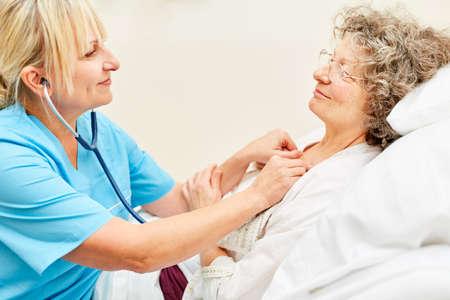 Female doctor or nurse examining an elderly woman at the hospital Banco de Imagens