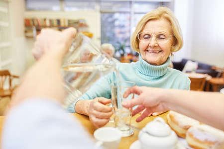 Geriatric nurse pours a glass of water into a senior citizen's home