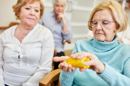 Elderly woman as patient takes pills in the health course in the old people's home