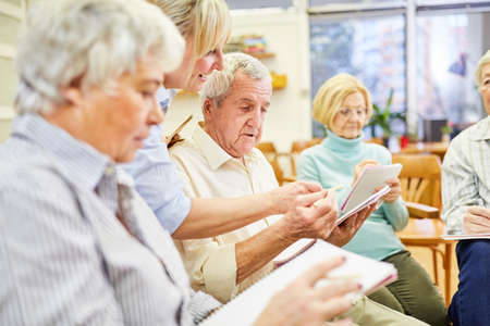 A doctor or therapist helps seniors write in writing therapy