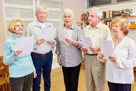 Group of seniors with dementia singing together in a choir rehearsal