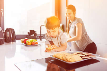 Little child eating biscuit in kitchen with laughing mother in the background