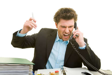 Young man talking on the phone in frustration at his desk