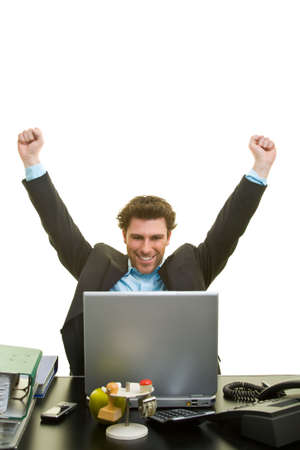 Young man in suit cheers at his desk in front of a laptop Banque d'images