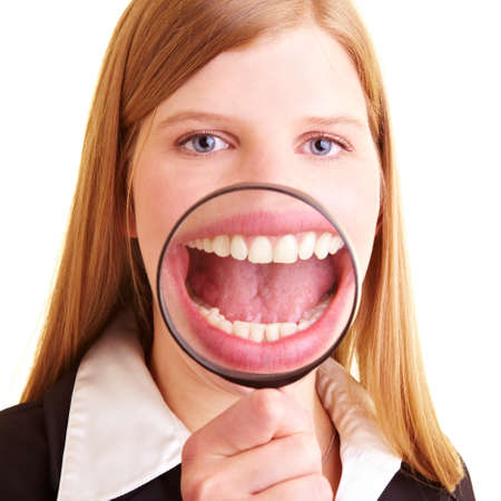 Laughing businesswoman holds a magnifying glass in front of her mouth
