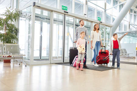 Happy family and two kids with luggage in airport terminal on the road on vacation