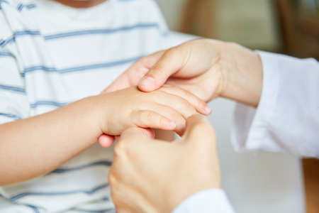 Doctor or osteopath is doing acupressure on the hand of a child because of pain