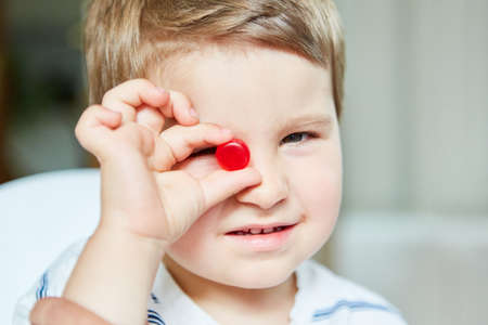 Little boy holds a red candy in one hand