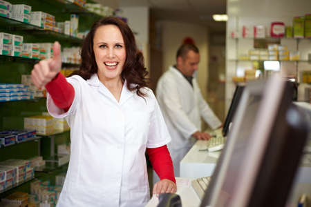 Laughing pharmacist in pharmacy holds her thumb up