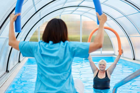 Therapist with swimming noodle shows a senior woman doing aquagym exercise