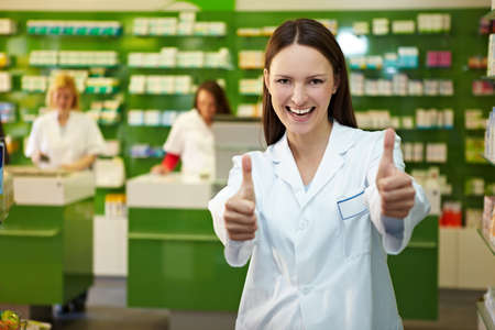 Laughing pharmacist in pharmacy holds both thumbs up