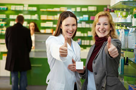 Pharmacist and customer in pharmacy hold their thumbs up 免版税图像