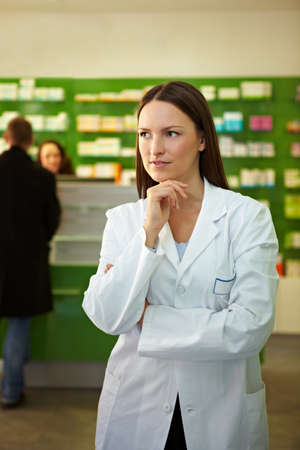 Thoughtful pharmacist stands in a pharmacy 免版税图像