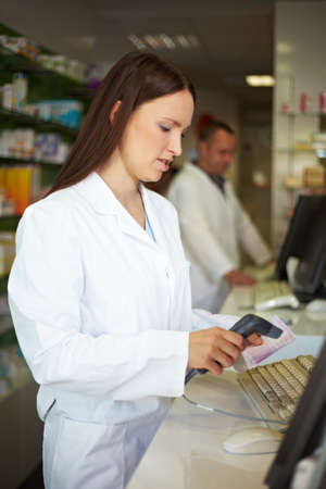 Pharmacist in pharmacy scans a prescription
