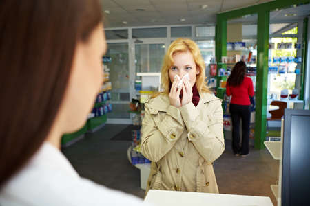 Woman stands with a cold at the cash register of a pharmacy