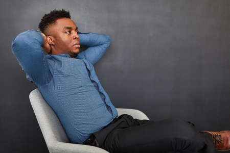 African businessman leaning back thoughtfully against a gray wall