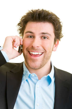 Young man in business attire is talking on his cell phone while laughing