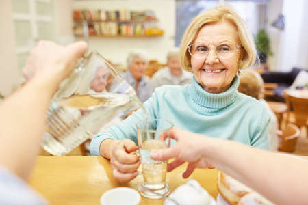 Geriatric nurse pours water from a carafe into the glass of a smiling elderly woman