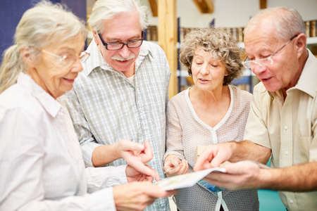 Senior group with book in the library in retirement home has fun learning
