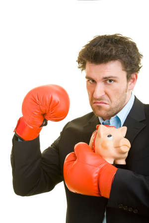 Young man in suit defends his piggy bank with red boxing gloves
