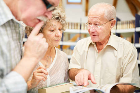 Three seniors read together in a book in the library in the retirement home
