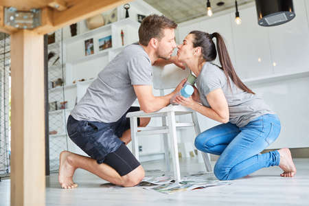 Young handyman couple kissing while refurbishing furniture and painting chair