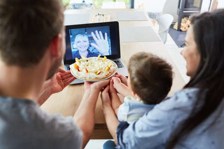 Family with child in video chat with grandmother on birthday showing homemade cake