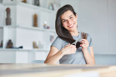 Happy young woman using scissors at home while cutting her long hair by herself