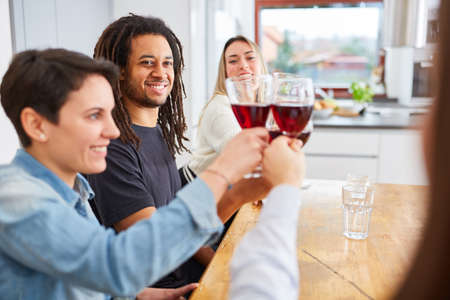 Happy group of friends toasting together with glass of red wine at home