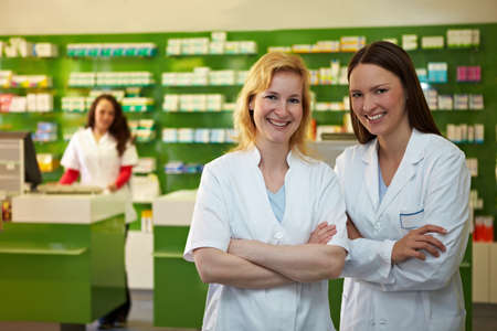 Two laughing pharmacists are happy in a pharmacy