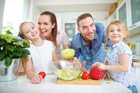 Happy family lives vegan and stands in the kitchen with fresh vegetables