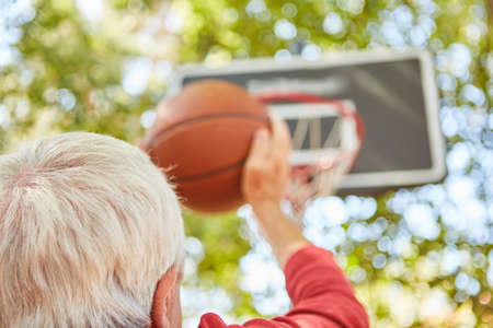 Senior man with ball concentrates on free throw while playing basketball in the garden