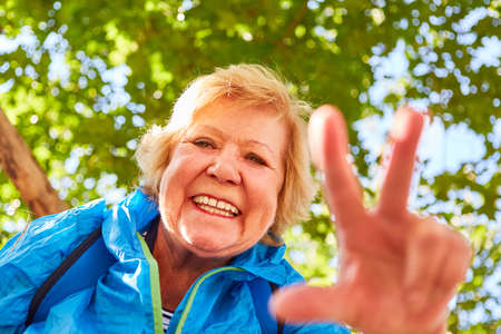 Happy and vital senior woman on a hike in nature in summer Stock Photo