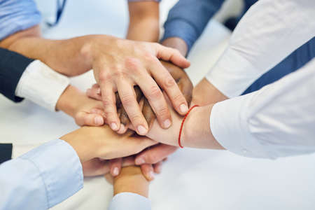 Managers stack many hands in business team building meeting