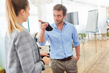 Businessman admonishes colleague with an outstretched index finger as criticism