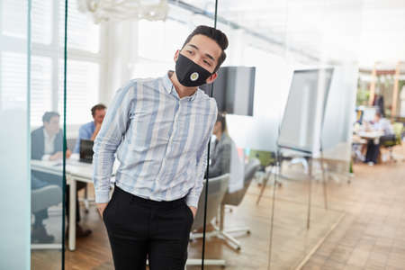 Businessman with face mask because of Covid-19 and coronavirus looks curious