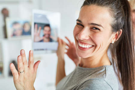 Happy young woman using tablet computer while video chat online with her partner