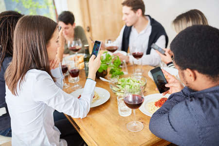 Distracted friends all look at their smartphone while having lunch together at the table
