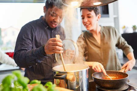 Friends cooking pasta with sauce together in shared kitchen for shared dining Stock Photo