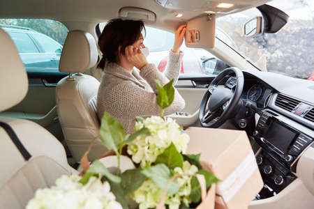 Car driver with face mask and packages in the interior makes a call as a delivery service concept Standard-Bild