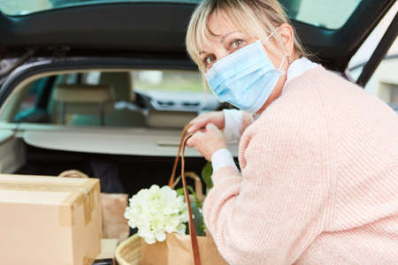 Woman with face mask has bag with purchases in her hands in front of a full car trunk