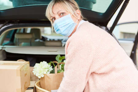 Woman with face mask in front of an open car trunk full of packages and purchases