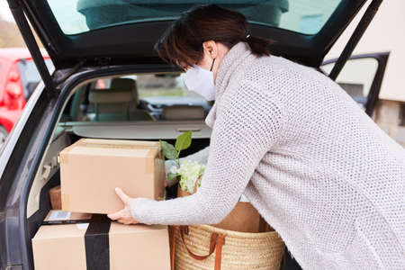 Woman with face mask loads full car trunk with packages and purchases