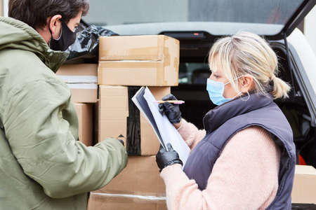 Parcel service team checks deliveries in front of an open loading space with many parcels