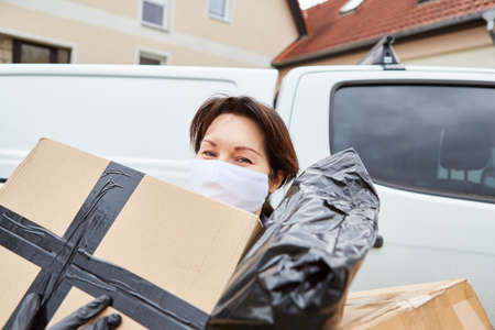 Delivery service parcel carrier with face mask outside carries out many parcels for delivery