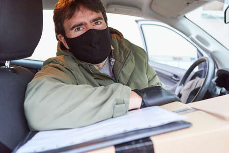 Parcel carrier brings packages with face masks because of Covid-19 in the car for Christmas Standard-Bild