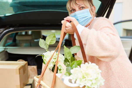 Woman with face mask holds bag with flowers in hands in front of full car trunk