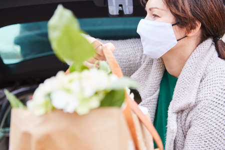 Woman with surgical mask carries bag with flowers in hands out of car trunk