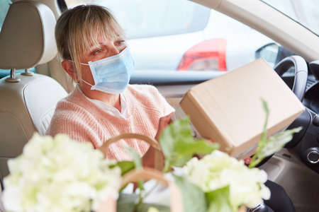 Woman wears face mask and checks package in the interior of her car before delivery or after collection Standard-Bild